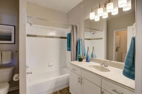 Bathroom with vanity sink area with light on for apartment building
