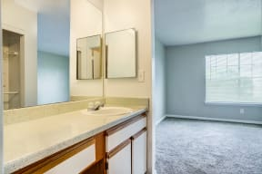 Bathroom vanity with entry way to bedroom. White cabinets with tan counter tops and mounted mirror