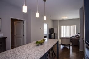 Large Kitchen Island with Granite Countertops and Pendant Lighting