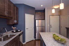 Spacious Kitchen with Dark Wood Cabinetry, Granite Countertops and Stainless Steel Appliances