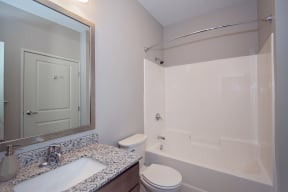 Spacious Bathroom with Granite Countertop Vanity and Shower with Tub