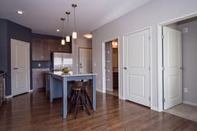 Spacious Open Concept Living with Hardwood Style Flooring and White Trim