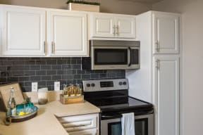Kitchen with White Cabinetry, Stainless Steel Appliances and Hardware with Grey Subway Tile Backsplash