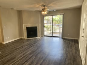 spacious living room with wood plank floors and fire place at Avisa Lakes Apartments