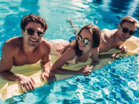 three young adults on a floatie in a pool