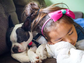 a child and a dog snuggling together