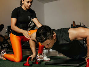 a young woman spotting while a young man does push ups in a gym