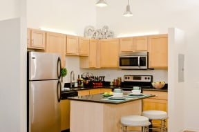 Granite countertops & stainless steel appliances are standard in Ovaltine Court kitchens.