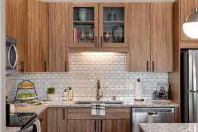 Wood cabinets and tile backsplash in Kitchen at Modern kitchen at Nuvelo at Parkside Apartments