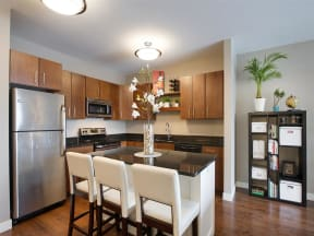 Be @ The Calhoun Greenway Apartment Kitchen with Wood Cabinets, Black Granite Island, and Stainless-Steel Appliances