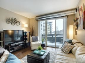 Be @ The Calhoun Greenway Large Apartment Living Room with sliding door access to balcony and studio lights