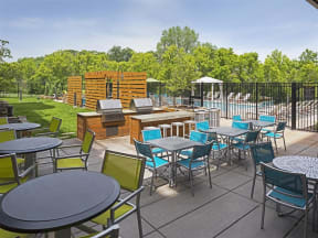 Be @ The Calhoun Greenway Outdoor Sitting Area with blue and green chairs and steel tables