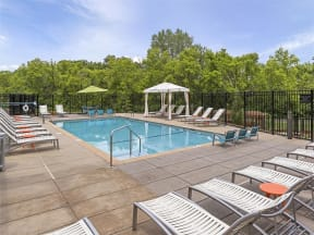 Be @ The Calhoun Greenway Large blue pool with cabana and chairs around it