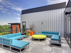 Be @ The Calhoun Greenway Rooftop Patio lounge area with blue couches and green sofa table