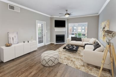 Model Living Room with TV above fireplace with patio door and large window