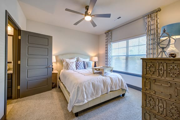 master bedroom with large windows and ceiling fan