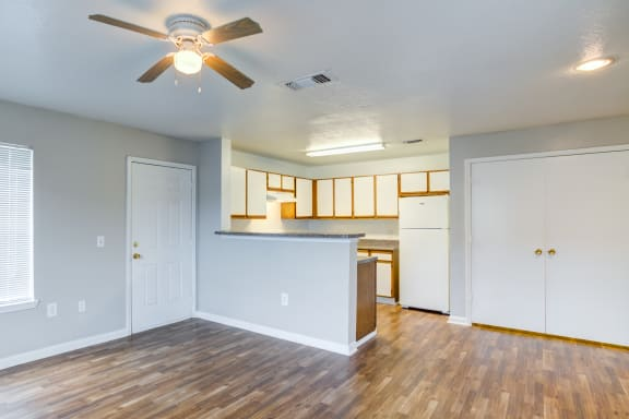 Vacant interior, featured from living room overlooking kitchen, brown wood style flooring, ceiling fan, white cabinets with wood style trim, and white fridge