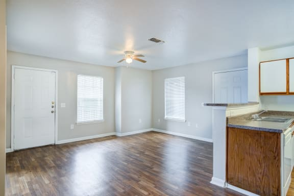 Vacant living room with front door, two single windows, ceiling fan, brown wood style flooring and cream colored walls