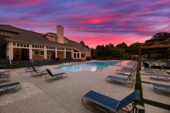 swimming pool with clubhouse in the background at sunset