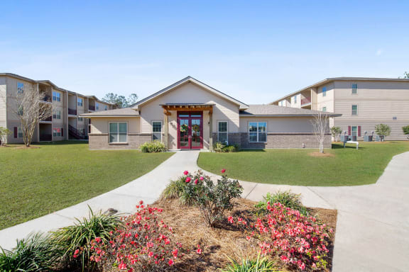 Leasing office entrance of Reagan Crossing apartments in Covington, AL with well-maintained landscape and pathways