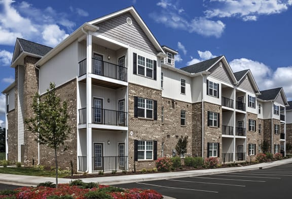 Exterior of the 3-story apartment building at The Retreat at the Park in Burlington, NC showing the patios and balconies