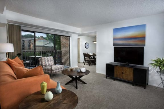 living room at Vistas of Annandale apartments in Annandale, VA with couch, chair, coffee table, TV and console table