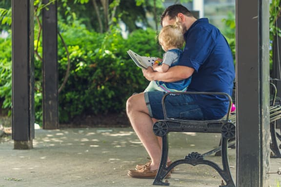 Family Reading Outside at Cypress Point Apartments, California