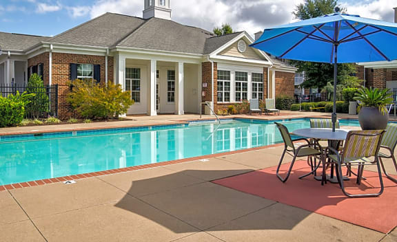 pool and sundeck with tables and umbrellas by clubhouse