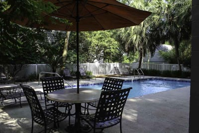 pool with sundeck and covered lounge areas