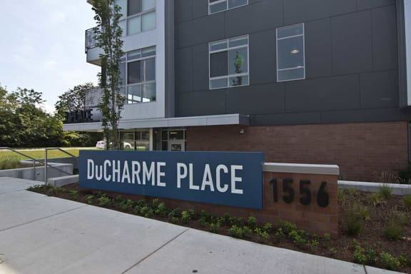Exterior image of DuCharme Place's monument sign. Grey building is in background.