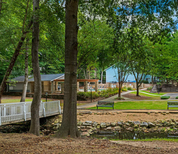 Landscaping and grounds around the apartments, with a bridge, creek and benches