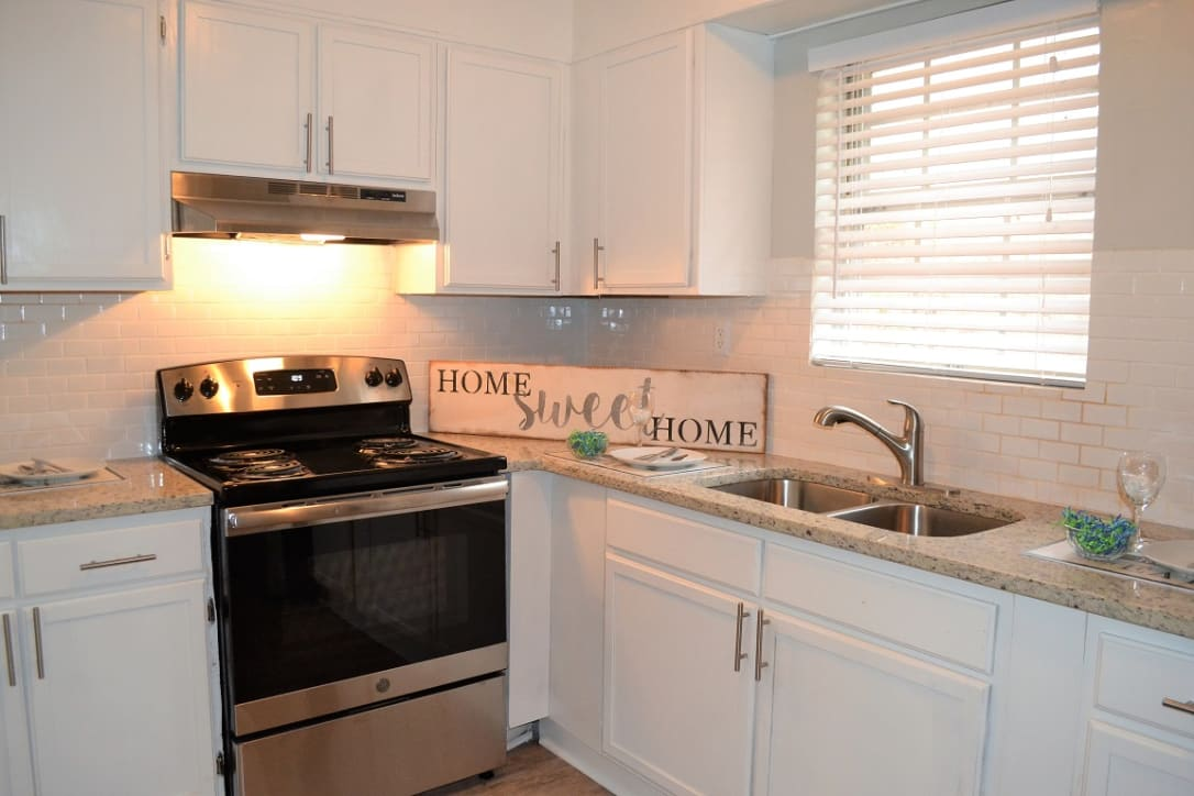 renovated kitchen, white cabinets, quartz couter top, stainless steel stove, subway tile backsplash