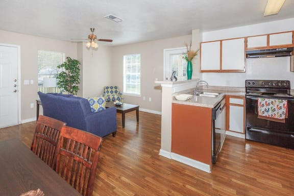 Kitchen overlooking living room side by side with dining room, wood style flooring, tan walls and white trim