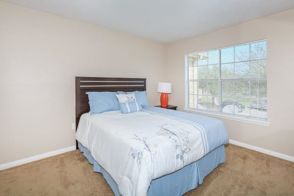 bedroom with tan carpet, double windows, tan walls and white trimming, full size bed