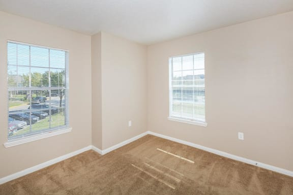 Vacant bedroom with two single windows, tan carpet, tan walls with white trimming