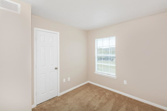 bedroom with single closet door, single window with blinds, tan carpet, tan walls with white trimming