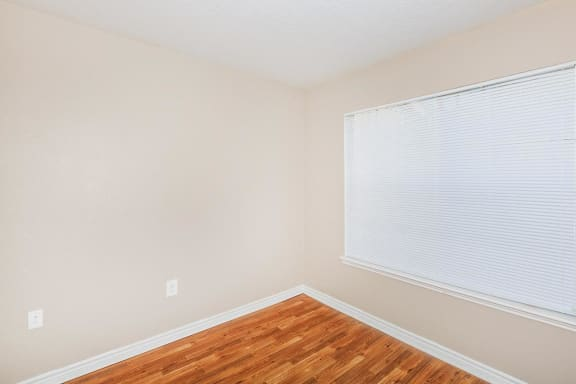Vacant bedroom with double windows and blinds, tan walls with white trimming, brown wood style flooring