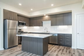 Apartments for Rent in Folsom - Hub Apartments - Luxury Kitchen with White Kitchen Island, Stainless Steel Appliances, and Wood-Style Flooring