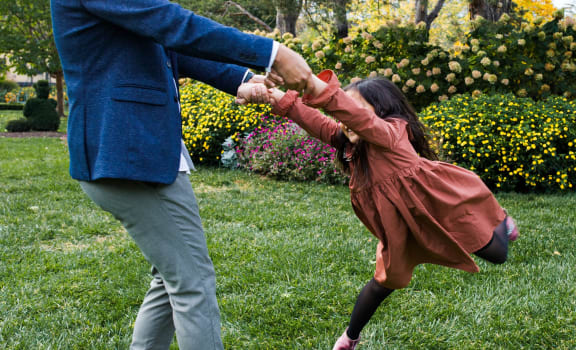 Little Girl Being Spun Around by Adult in Grassy Field