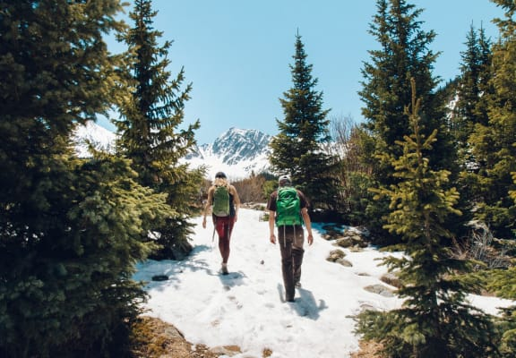 Couple Hiking Through Snowy Forest Mountain