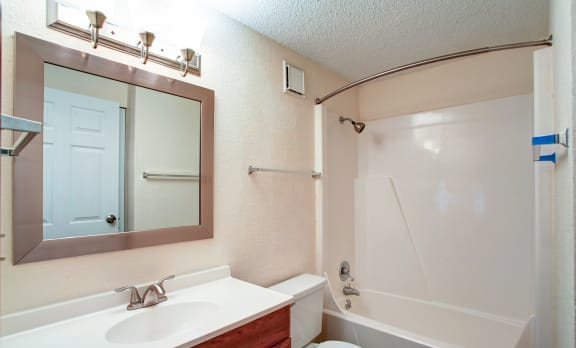 Bathroom with tub and shower combination, white toilet, and sink with brown cabinets.