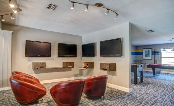 Gaming/media room with four wall mounted TV's and four arm chairs.