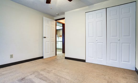 Bedroom with beige carpeting, white closet doors, and light tan walls.