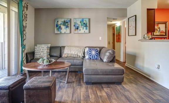 Living room with wood style floors, gray couch, drapery, coffee table, and wall art.
