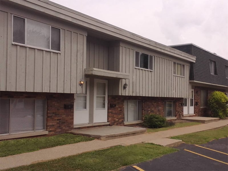 Exterior of Parkview Townhomes. With sidewalk and green grass. Buildings lower half is brick and upper is grey siding.