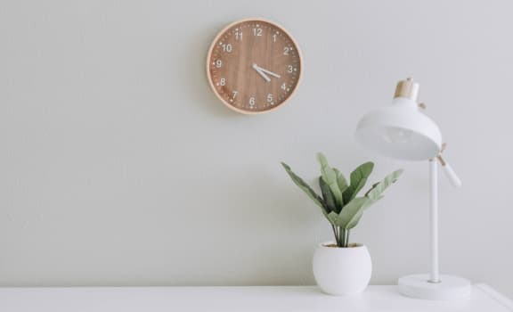 Lamp and plant on white desk near wall with clock