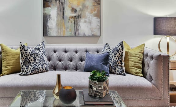 Gray couch with coffee table, lamp, throw pillows, and flower vase