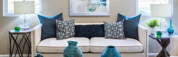 White couch with blue throw pillows, end tables, lamps, and tabletop decor