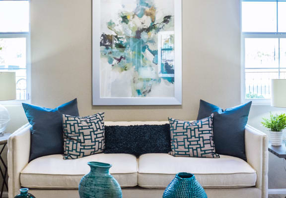 Couch against wall with windows and blue pillows