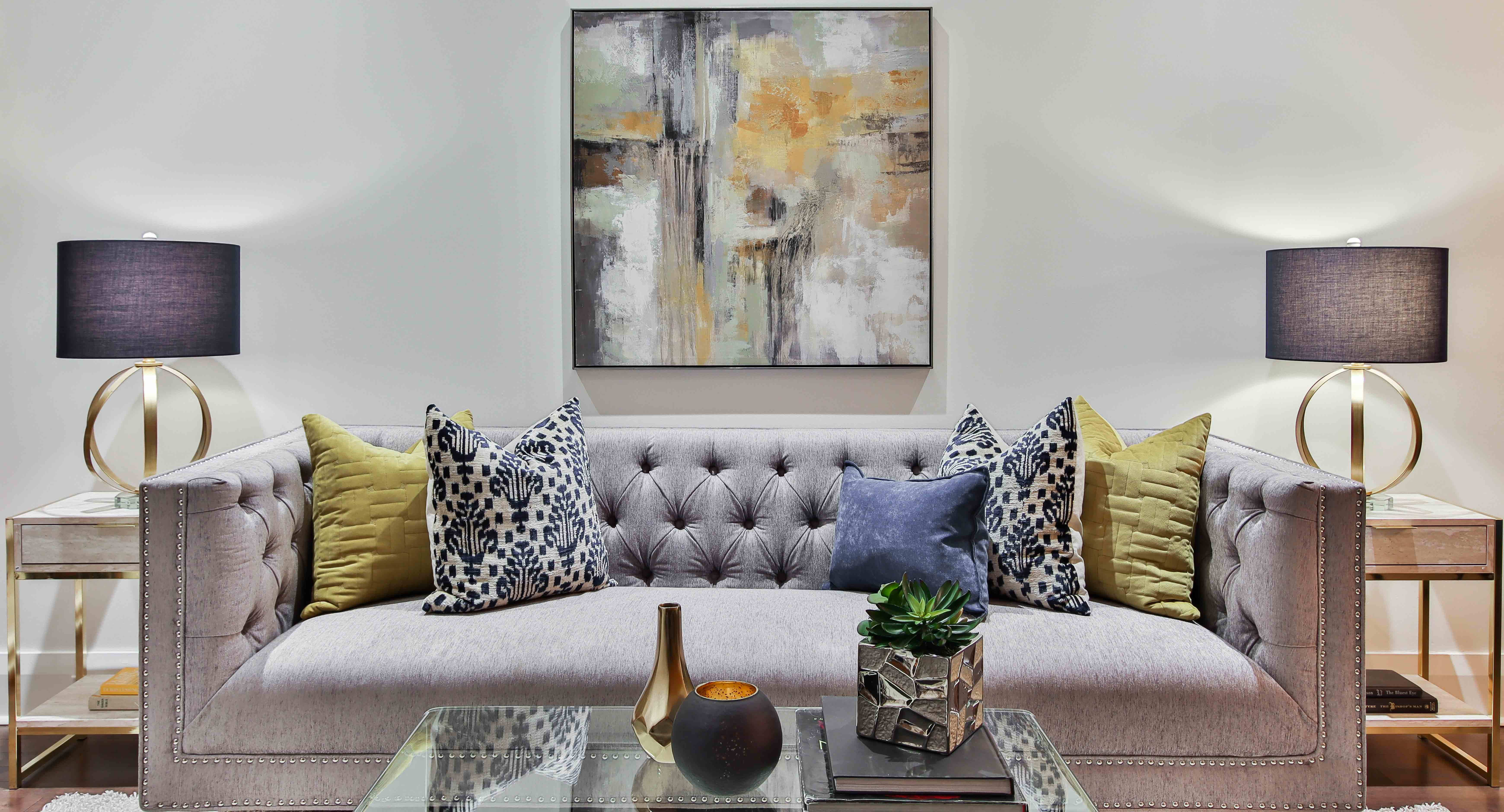 Plush couch with throw pillows, coffee table, trinkets, lamps, and large wall art above